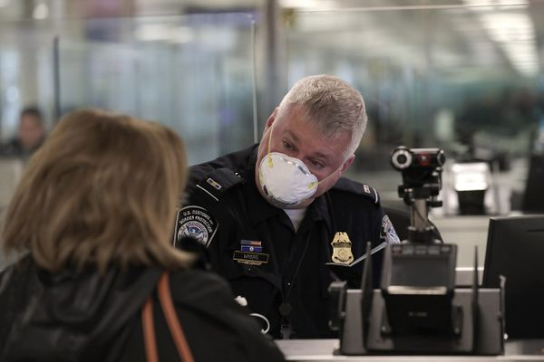 An officer with U.S. Customs and Border Protection Office of Field Operations welcomes and clears international travelers arriving at Dulles International Airport in Dulles, Va., March 13, 2020.