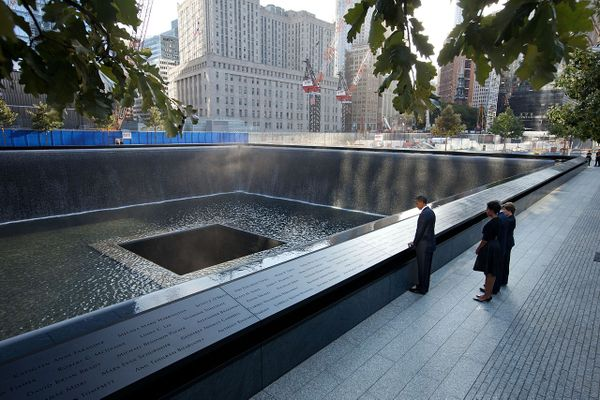 President Barack Obama and First Lady Michelle Obama, along with former President George W. Bush and former First Lady Laura Bush, pause at the North Memorial Pool of the National September 11 Memorial in New York, N.Y., on the tenth anniversary of the 9/11 attacks against the United States, Sunday, Sept. 11, 2011.