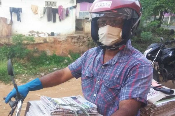 A Newspaper vendor in Tamil Nadu, India, wearing safety gloves, mask and safety glass.