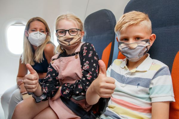 Children using face mask on an airplane