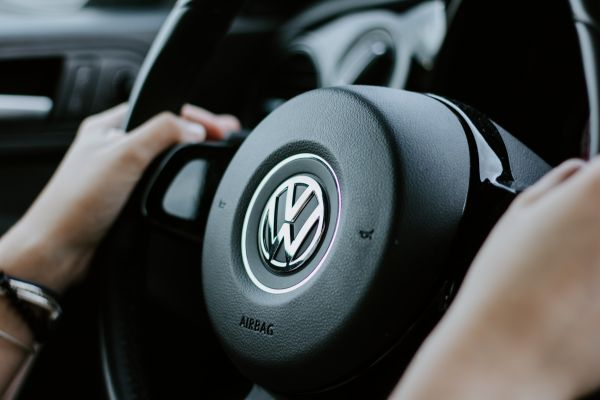 Person holding black Volkswagen steering wheel