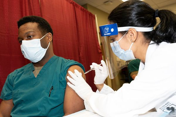 Army Cpt. Isaiah Horton, a doctor at Walter Reed National Military Medical Center, receives a COVID-19 vaccination