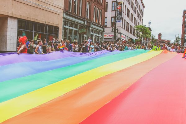 Portland, Maine residents carry the large rainbow flag down Congress Street