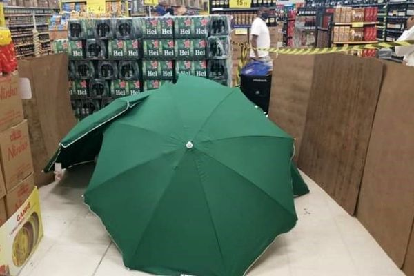 Umbrellas covering the body of a deceased worker