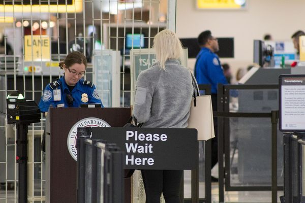 A Transportation Security Administration agent at a checkpoint verifying passenger identification, John Glenn Columbus International Airport